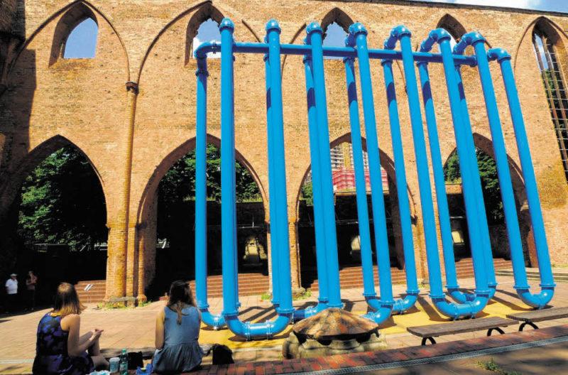 Blaue Rohre vor Backstein