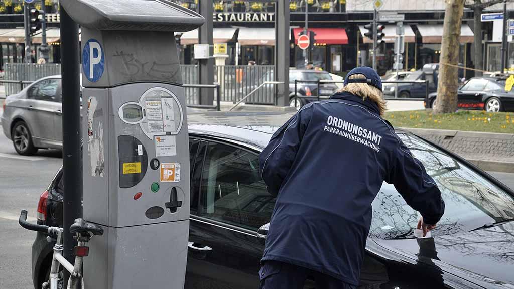 Ordnungsamt und Parksünder, Ordnungsamt, Frau, Parkraumüberwachung, Parkautomat, Auto, Parksünder, Knöllchen, Bußgeldbe