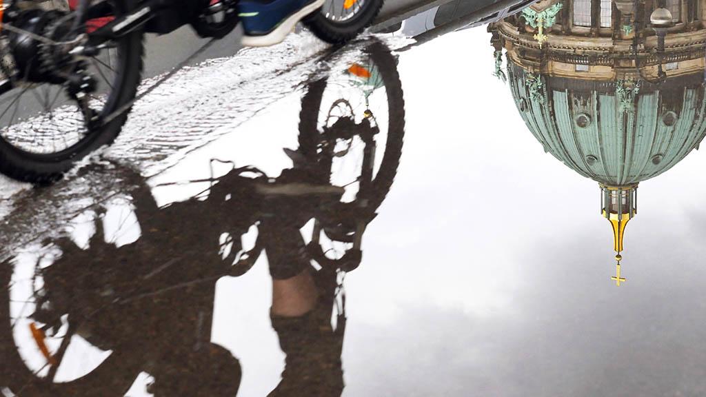 Radfahrer spiegelt sich in einer Pfütze